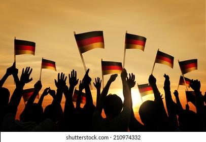 Group of People Waving German Flags in Back Lit