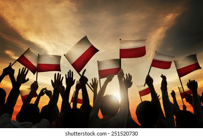 Group of People Waving Polish Flags in Back Lit