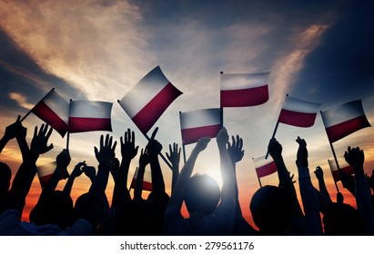 Group of People Waving Polish Flags in Back Lit Concept