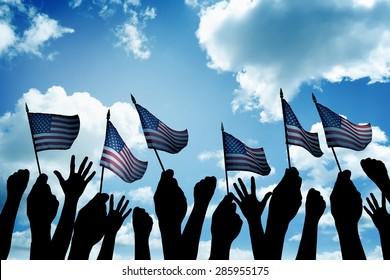 Group of people waving small USA flag facing blue sky