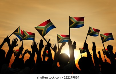 Group of People Waving South African Flags in Back Lit