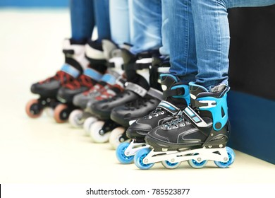 Group of people wearing roller skates on light background