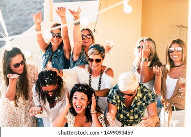 Group of people women friends have fun together celebrating with confetti and happiness - concept of friendship and event celebration