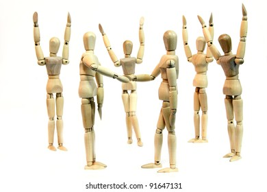A group of people (wooden doll) cheering when two person shake hand depicting a deal or agreement