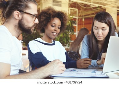 Group of people working on business project at cafe, sitting at table with sheets of paper and laptop, trying to find brand-new solutions for company's growth, looking thoughtful and concentrated