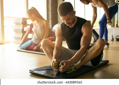 Group of people workout in healthy club. Young people stretching on floor.