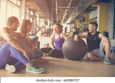 Group of people workout in healthy club. People having conversation after Pilates exercise with Pilates ball.
