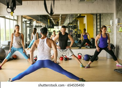 Group of people workout in healthy club. Young people stretching for legs.