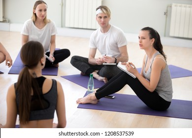 Group people at yoga sport seminar in professional training studio. Girls guys sitting together listen teacher ask questions communicating. Beginners wish explore more gain deeper knowledge about yoga