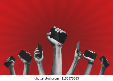 group of people's hands holding phones and rising them up against a red background