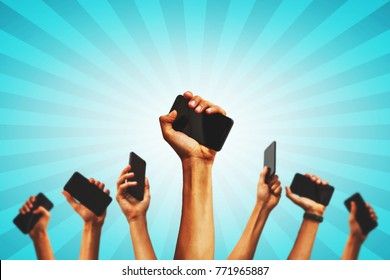 group of people's hands holding phones and rising them up
