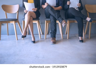 Group of peoples are sitting to review the documents while waiting for a job interview.