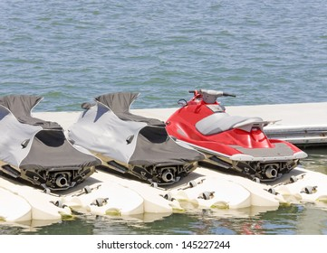 Group of personal water craft, jet skis at the dock. Bright red jet ski next to 2 covered jet skis docked at the marina in calm blue water. Rear view showing the jet nozzle. Horizontal view.