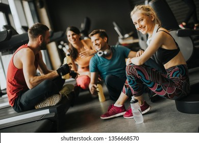 Group pf young people in sportswear talking and laughing together while resting in the gym after a workout