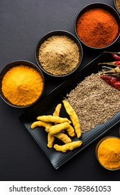 Group photo of four basic Indian spices like raw red chilli, turmeric, coriander and cumin powder. selective focus
