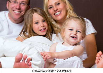 Group picture of a young family, father, mother and children in bedroom
