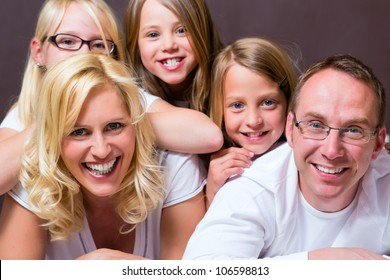 Group picture of a young family, father, mother and three children in bedroom