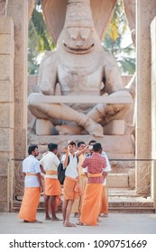 Group of pilgrims - Hindus dressed in orange clothes stands in front of Narasimha's - the angry embodiment of god Vishnu. The youngest of pilgrims takes a selfie India, Hampi, on January 10, 2018.