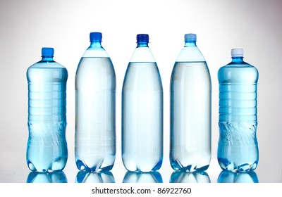 Group plastic bottles of water isolated on white