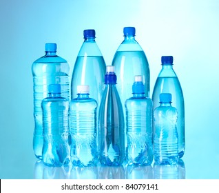 Group plastic bottles of water on blue background