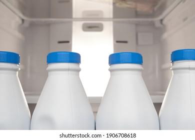 Groupe de bouteilles de lait en plastique entreposées et alignées dans la porte du réfrigérateur