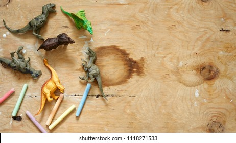 Group of a plastic toy dinosaurs with colorful crayons on a wooden background. Top view with copy space