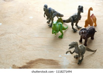Group of a plastic toy dinosaurs on a wooden background. Top view with copy space, selective focus