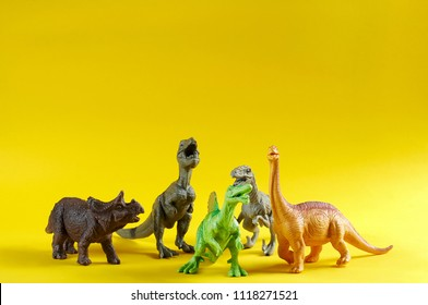 Group of a plastic toy dinosaurs: Tyrannosaurus rex, Spinosaurus, Triceratops, Carnosaur and Brachiosaurus on yellow background. Close up view with copy space