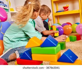 Group playing children of game blocks on floor in kindergarten .
