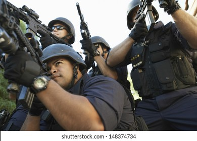 Group of police officers aiming with guns