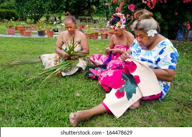 Group of Polynesian Pacific Island Tahitian senior females sewing Tivaivai and weaving a hat knees out of palm leaves in home garden in Aitutaki Island in the Cook Islands.Real people. Copy space