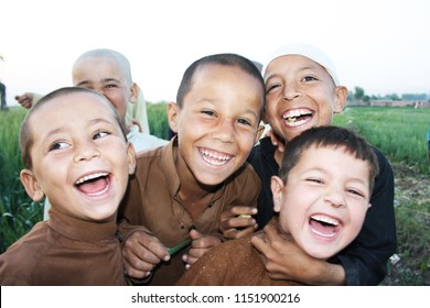 a group of poor labor kids are laughing and playing in a village in peshawar pakistan