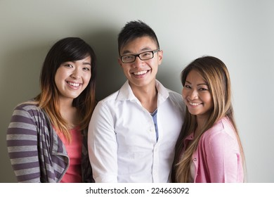 Group portrait of 3 happy Asian people. Looking at camera, in front of grey wall