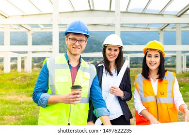 Group portrait of architect and construction workers in distribution warehouse