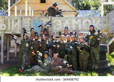 Group portrait of big happy company playing paintball and sign White Castle on background