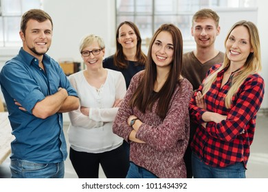 Group portrait of cheerful colleagues posing with arms crosses in office