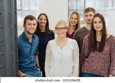 Group portrait of cheerful colleagues posing in office