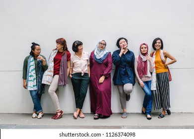 A group portrait of diverse Asian women (Malay and Chinese) posing with one another against a white wall. It is a fun portrait and they are all enjoying getting their photo being taken.
