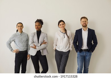 Group portrait of diverse office workers or job candidates. Team of happy confident multiracial business people in formal and smart casual wear standing near studio wall, smiling and looking at camera