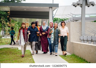 Group portrait of diverse group of women (Malay, Chinese and Eurasian) walking down a path in a housing estate in Singapore, Asia. They are friends and smiling as they walk and talk together.