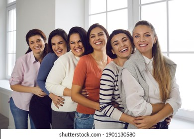 Group portrait of female friends hugging, smiling and looking at camera. Team of happy young women in their 20s and 30s standing in bright office and embracing each other. Concept of unity and support