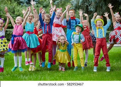 Group portrait of fifteen children dressed in bright dance suits jumping at grassy lawn with hands up.