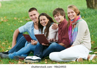 Group portrait of four smiling cheerful students outdoors in autumn