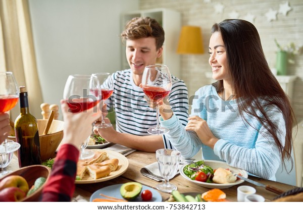 Group portrait of friends enjoying dinner together sitting at big table with delicious food , focus on young man and pretty Asian woman smiling happily clinking wine glasses celebrating holiday