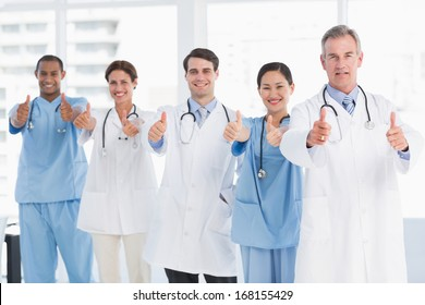 Group portrait of happy confident doctors gesturing thumbs up at hospital