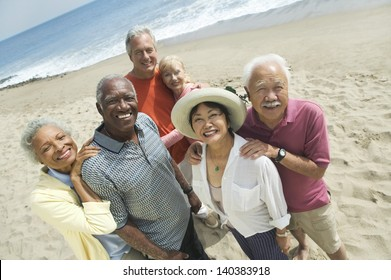 Group portrait of happy multiethnic couples smiling on the beach