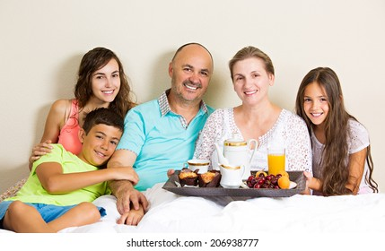 Group portrait happy, smiling, joyful family, mother, father, daughters, son having breakfast in bed, surprise on mom day. Positive human emotions, face expressions, feelings, life perception