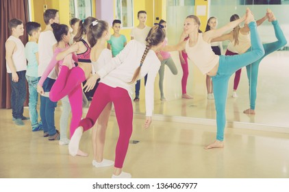 Group portrait of happy teenagers with female choreographer doing leg-split and crab position in a modern dance studio