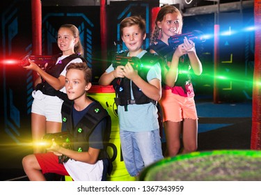 Group portrait of happy teenagers with laser guns having fun on dark lasertag arena