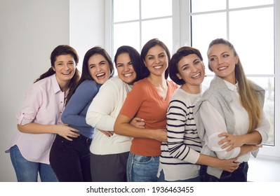 Group portrait of happy young women. Team of female friends or office coworkers in their 20s and 30s standing close together, smiling and looking at camera. Concept of unity and supporting each other